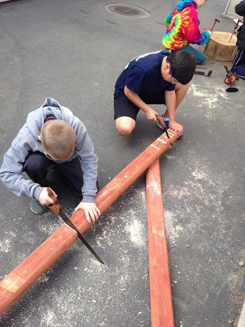 middle school boys sawing wood